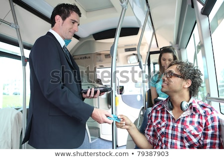 A young controller controlling passengers in a bus. Stock photo © photography33