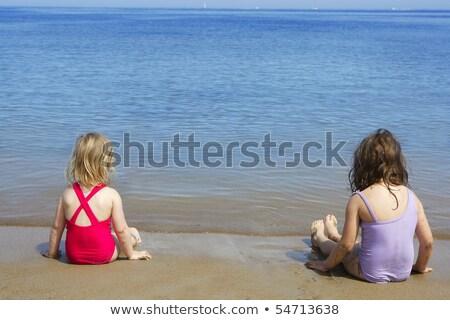 Nővérek ül tengerpart fürdőruha fürdőruha hátulnézet Stock fotó © lunamarina
