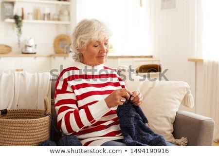 senior woman knitting on her sofa at home stock photo © hasloo