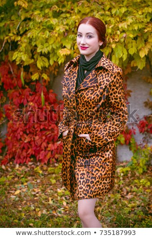 fashion woman in animal print coat posing for the camera stock photo © feedough