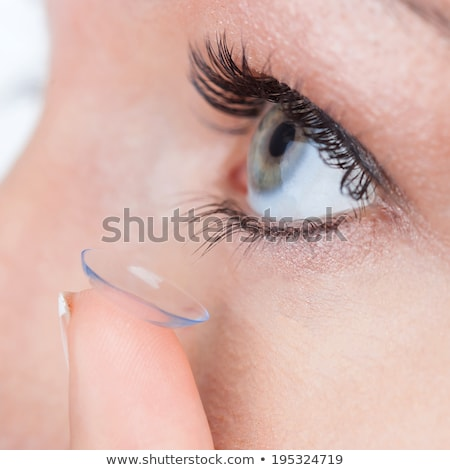 close up of blue woman eye with contact lens applying stock photo © cursedsenses