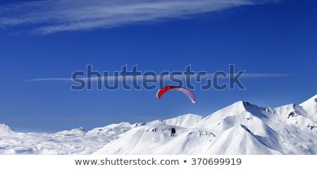 Stock photo: Paraglider in snowy mountains at nice sun day