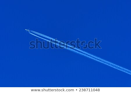 plane flying on a perfectly blue sky with Vapor Trail  Stock photo © meinzahn
