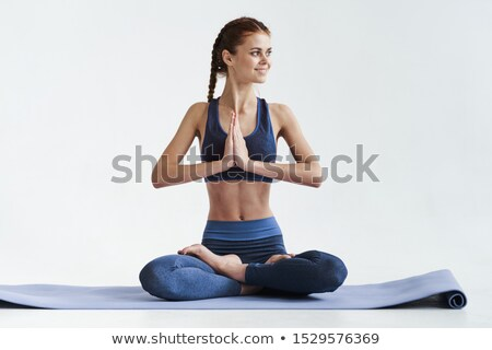 young beautiful fit woman sitting on the yoga mat at gym stock photo © deandrobot