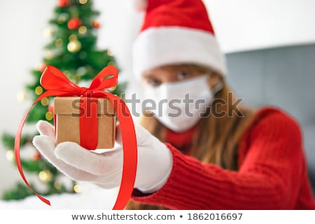 Young woman in a Santa hat holding out her hands Stock photo © juniart
