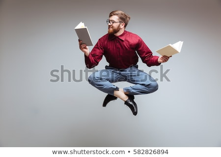 Portrait of a man reading a book. Isolated on gray stock photo © Patramansky
