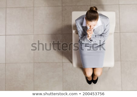 Thoughtful brunette woman sitting on the chair and looking away Stock photo © deandrobot