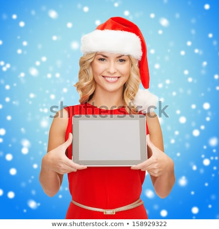 Smiling woman in santa claus hat showing blank screen tablet Stock photo © deandrobot