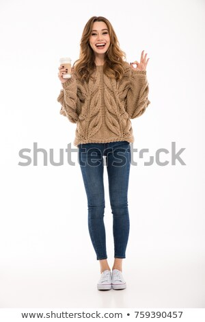 Woman dressed in warm sweater drinking coffee showing okay. Stock photo © deandrobot