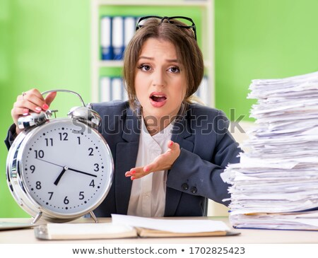 Young female employee very busy with ongoing paperwork Stock photo © Elnur