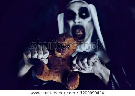frightening evil nun with a teddy bear stock photo © nito