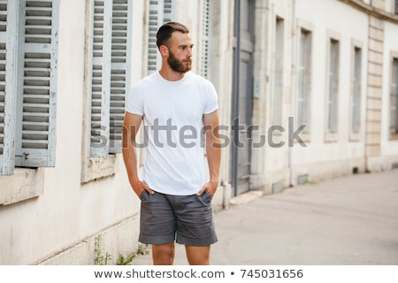 Portrait of a happy young bearded man in t-shirt Stock photo © deandrobot