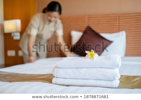Housemaid Placing Flowers On Stack Of Towels Stock photo © AndreyPopov