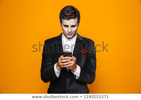 Photo of terrifying dead man on halloween wearing classical suit Stock photo © deandrobot