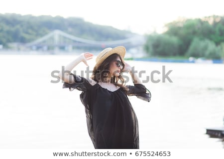 happy brunette woman in straw hat and sunglasses posing stock photo © deandrobot