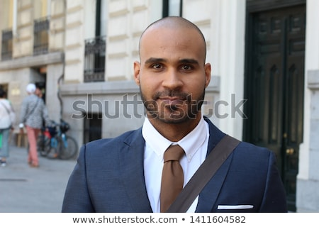 Portrait of positive handsome man 30s with tied hair smiling, an Stock photo © deandrobot