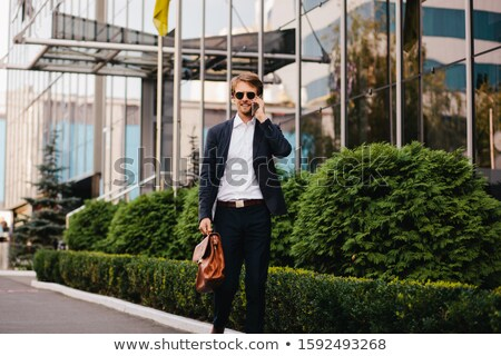 Image of happy smiling man in formal wear working and speaking o Stock photo © deandrobot