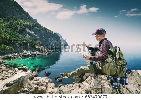Stock photo: Young Man Traveler with backpack, Viewing map relaxing outdoor o