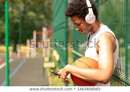 young contemporary basketball player in headphones scrolling in smartphone stock photo © pressmaster
