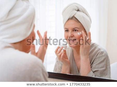 smiling senior woman applying cream to her face stock photo © dolgachov