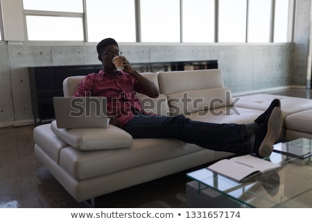 Front view of handsome African-american male executive relaxing on couch while having coffee and usi Stock photo © wavebreak_media