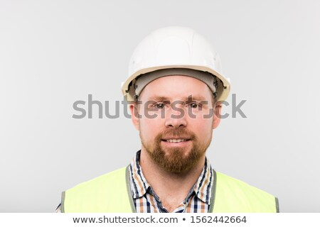 Young successful builder in white hardhat, checkered shirt and yellow vest Stock photo © pressmaster