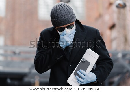 Infected young man has sneezing and coughing, wears disposable p Stock photo © vkstudio