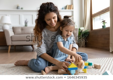Happy family embracing and sitting on the floor in front of Chri Stock photo © HASLOO