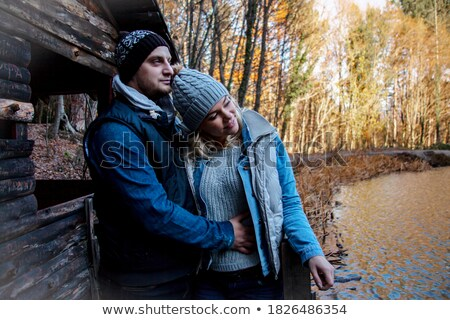 a young man dressed in coat and a young blonde woman posing near a tree Stock photo © photography33