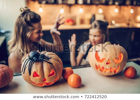 Stock photo: Little girl with parents preparing pumpkin for Halloween