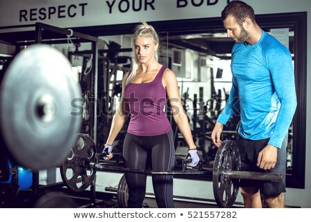 Gymnasium personal trainer man gewichtheffen bar vrouw Stockfoto © lunamarina