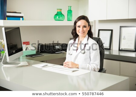 Doctor sitting behind her desk Stock photo © photography33