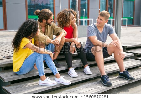 Pretty Female Friends Sitting on Wooden Stairs Stock photo © belahoche