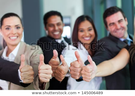 Cheerful business group giving thumbs up Stock photo © HASLOO