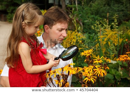 Little girl in red dress with father, considers plants through magnifying glass. stock photo © Paha_L