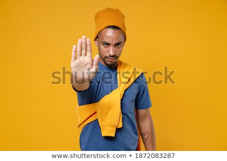 Young man in a hat showing stop gesture Stock photo © deandrobot