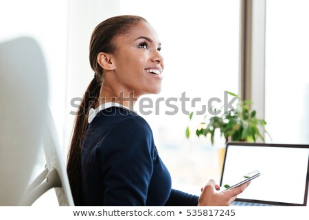 Woman in black dress sitting on chair and looking up Stock photo © deandrobot