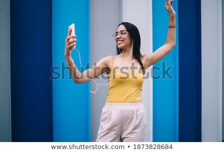 Millennial with Smartphones Earphone and Glasses Stock photo © Jesussanz