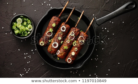 Barbecued turkey kebab decorated with fresh onion Stock photo © dash