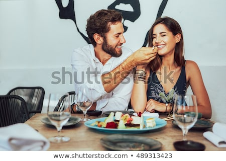 loving couple sitting in cafe eat desserts and drinking tea man take a photo by phone of his girlfr stock photo © deandrobot