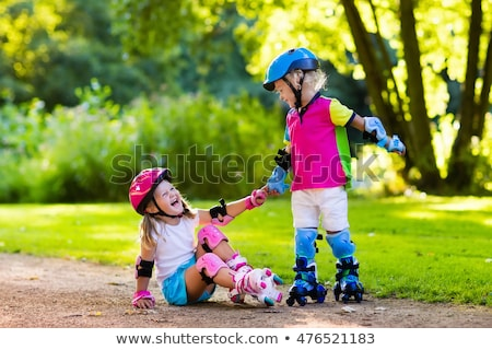 Two girls friends sisters on rollers in park outdoors holding sweeties candy. Stock photo © deandrobot