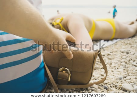 Thief Stealing From A Woman's Bag On The Beach Stock photo © AndreyPopov