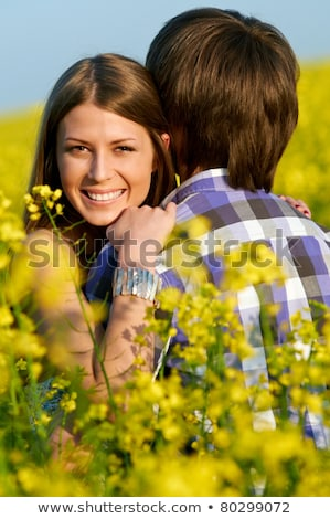 happy smiling young couple over yellow green rape meadow stock photo © lopolo