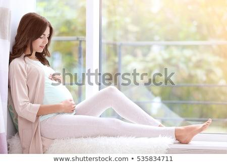 Genç güzel hamile kadın oturma pencere eşiği ev Stok fotoğraf © Lopolo