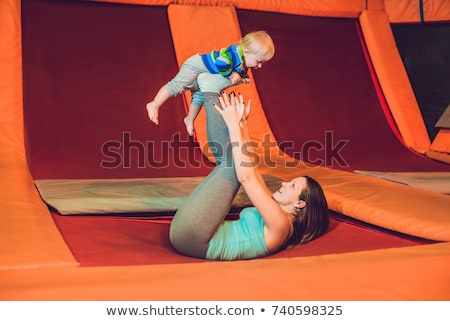 Mother And her son jumping on a trampoline in fitness park and doing exersice indoors Stock photo © galitskaya