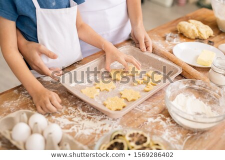Hand of youngster putting raw biscuits on tray while helping mom Stock photo © pressmaster