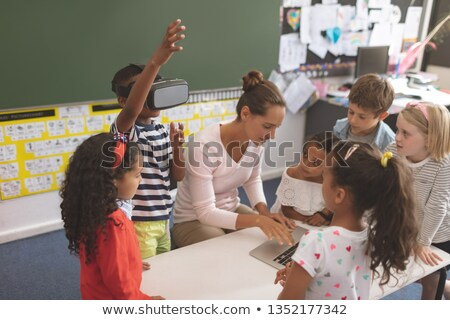 Front view of a schoolboy using virtual reality headset while teacher using laptop at school in clas Stock photo © wavebreak_media