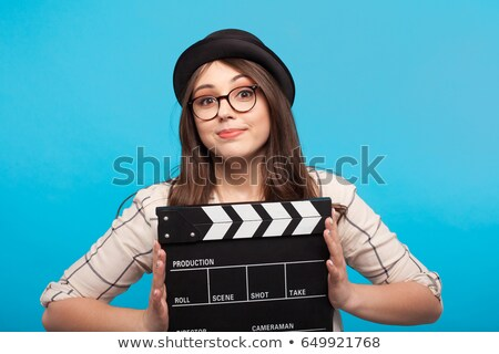 Smiling girl holding clapperboard Stock photo © stockyimages