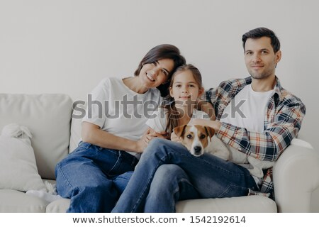 Mother, daughter and white dog sitting in a white living room Stock photo © photography33