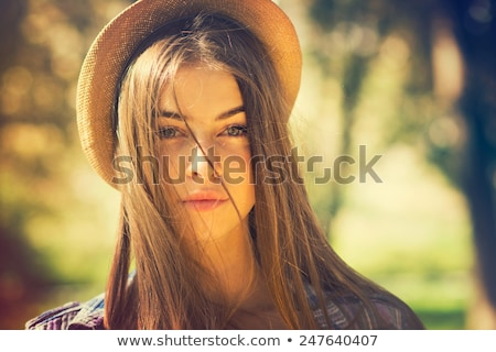 beautiful young brunette woman with brown eyes and long hair gently touching her face stock photo © nejron